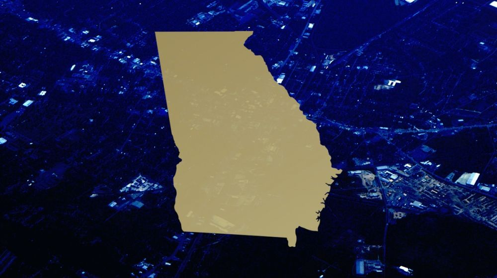 Graphic outline of the state of Georgia, overlaid on a stylized aerial image of Valdosta, Georgia